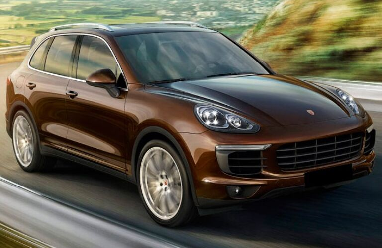 Exterior view of a brown 2017 Porsche Cayenne driving down the highway