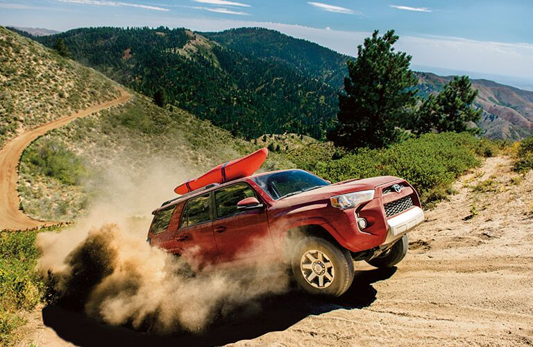 Red 2017 Toyota 4Runner Climbing Dirt Trail