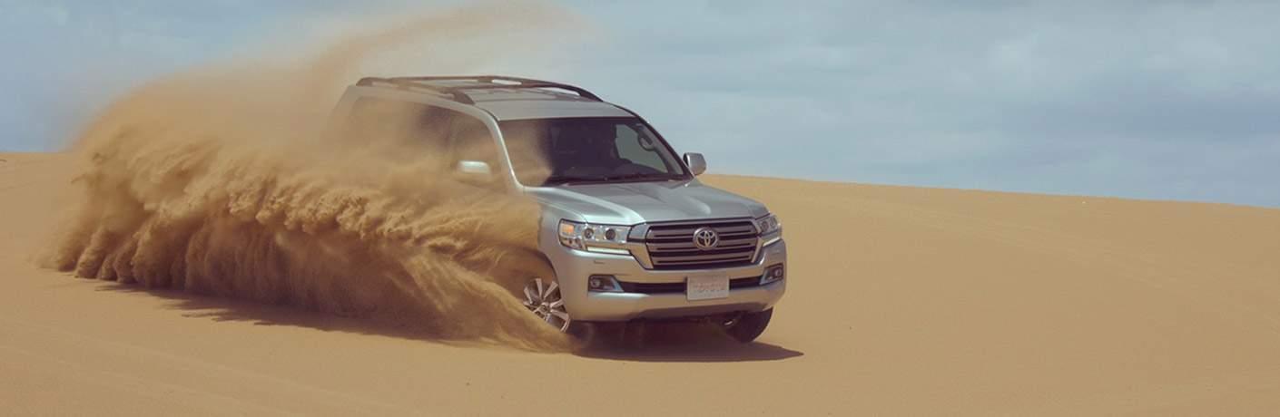 Silver 2018 Toyota Land Cruiser Kicking Up Sand in Desert