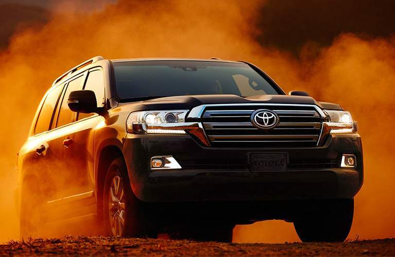 Black 2018 Toyota Land Cruiser on Dirt Road in a Dust Cloud
