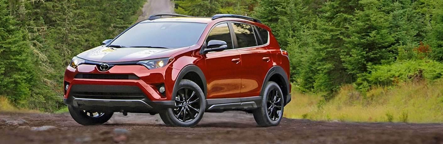 Red 2018 Toyota RAV4 Adventure with Black Graphics and Wheels on Country Road