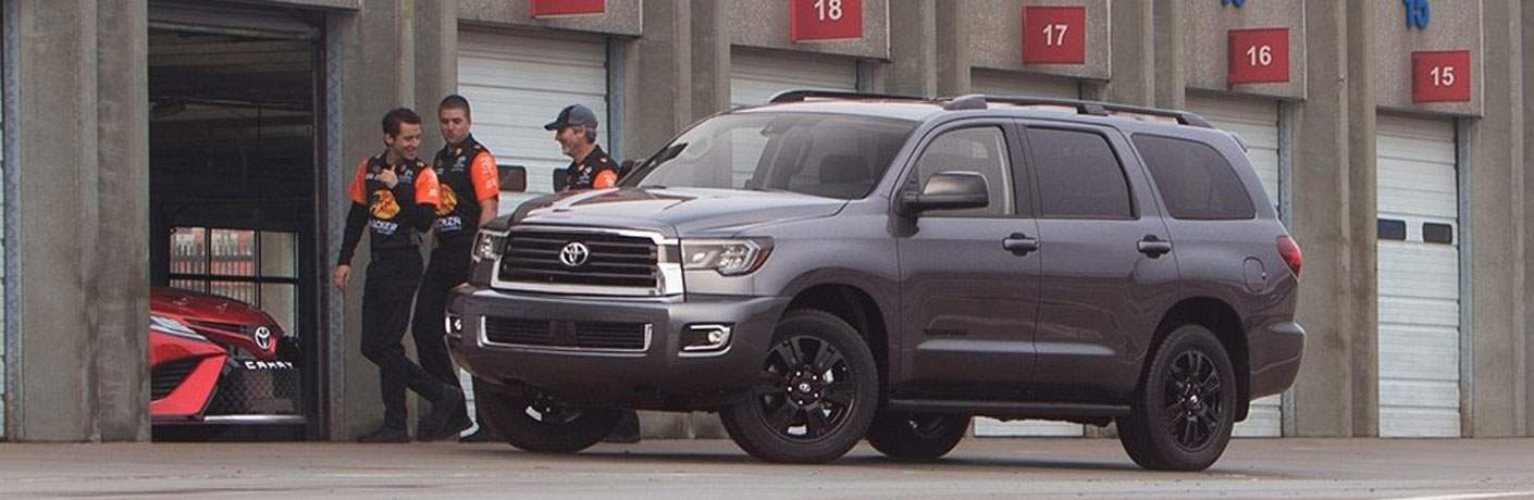 Gray 2018 Toyota Sequoia TRD Sport in Front of Race Track Garage with Pit Crew
