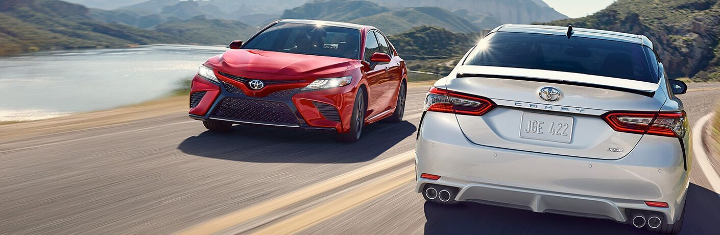 Red and Silver 2019 Toyota Camry Models Passing Each Other on a Coast Road