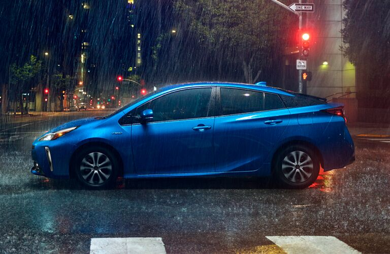 Blue 2019 Toyota Prius Side Exterior in the Rain on a City Street