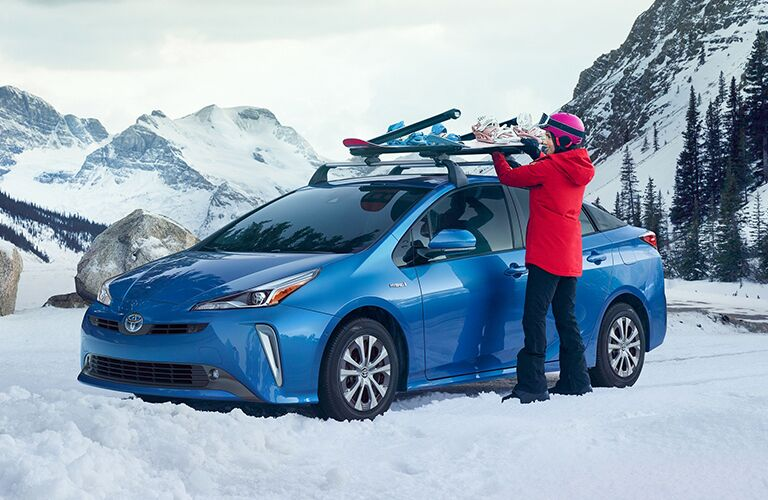Woman Putting a Snowboard on Roof Rack of Blue 2020 Toyota Prius in the Snow