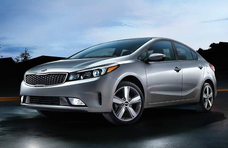 Silver 2018 Kia Forte Driving by Some Houses