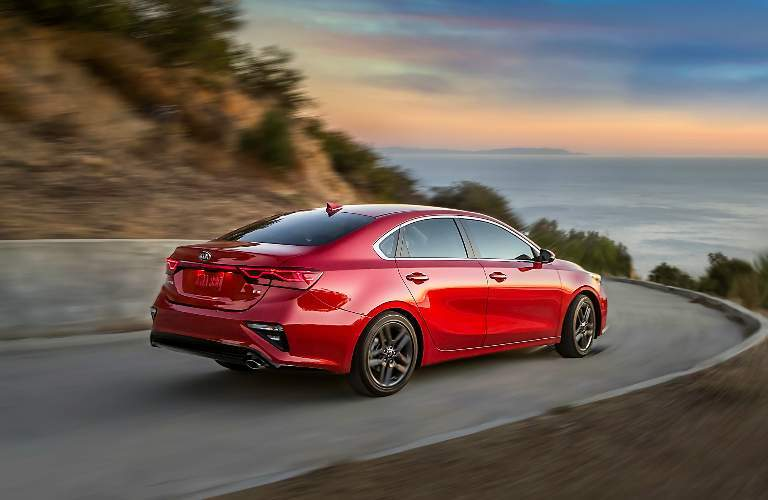 Red 2019 Kia Forte Driving on a Curvy Coastal Road