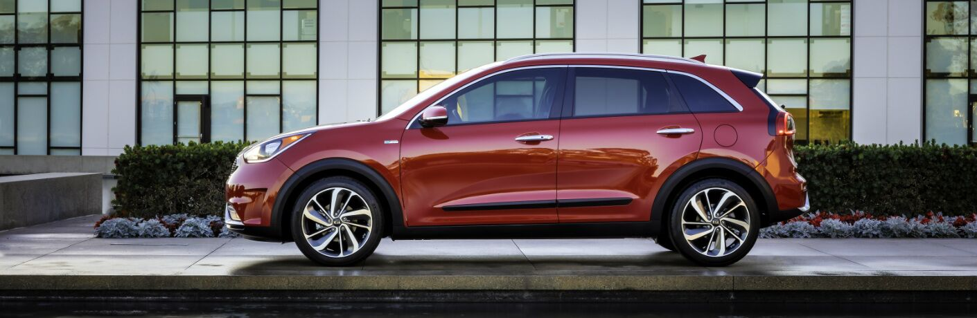 Red 2019 Kia Niro Parked in Front of a Building with Large Windows