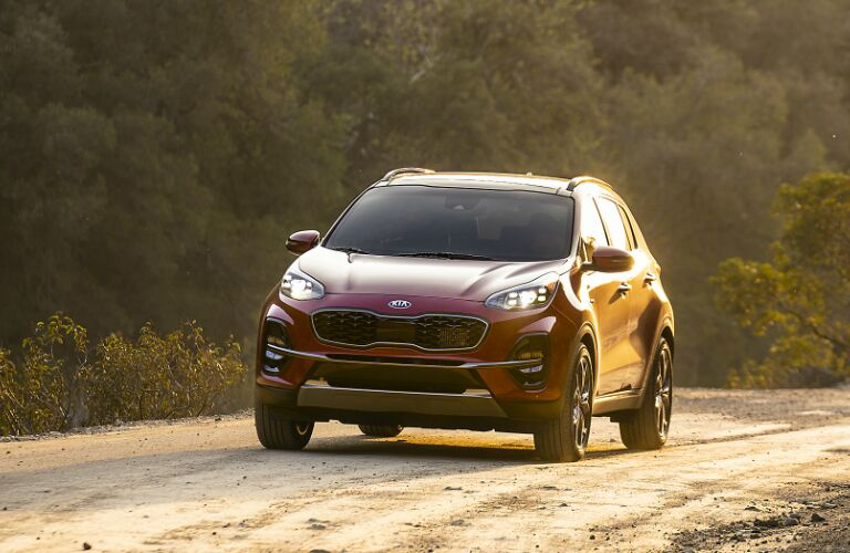 Red 2020 Kia Sportage driving on a dirt road