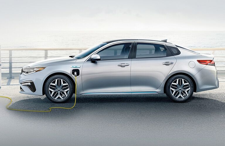 A charger plugged into a silver 2020 Kia Optima Plug-In Hybrid