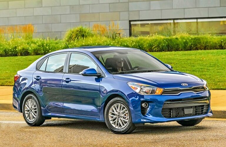 Blue 2020 Kia Rio driving by a large building