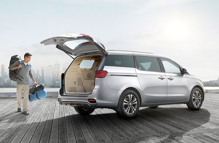 A man taking bags to the cargo area of a silver 2020 Kia Sedona