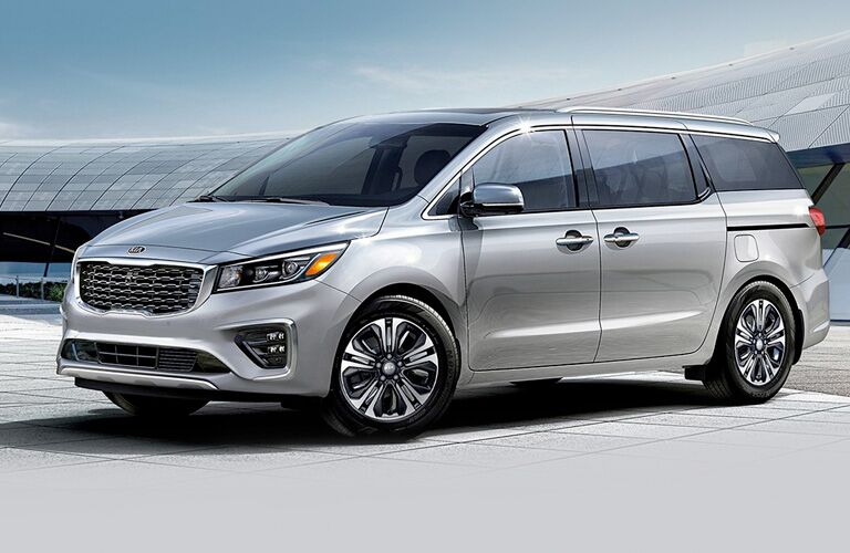 Silver 2020 Kia Sedona parked in front a large modernistic building