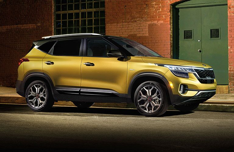 Yellow 2021 Kia Seltos parked next to a brick building