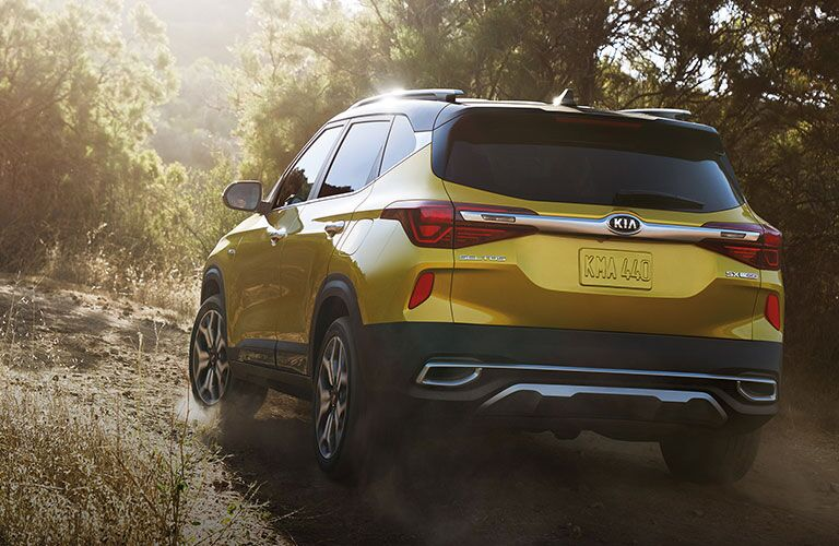 Yellow 2021 Kia Seltos driving on a road through a forest