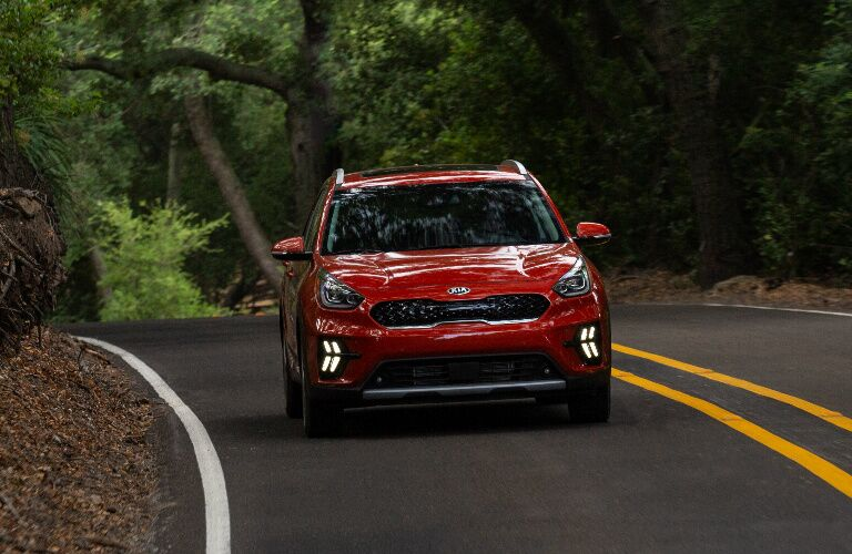 Red 2020 Kia Niro driving on a road through a forest