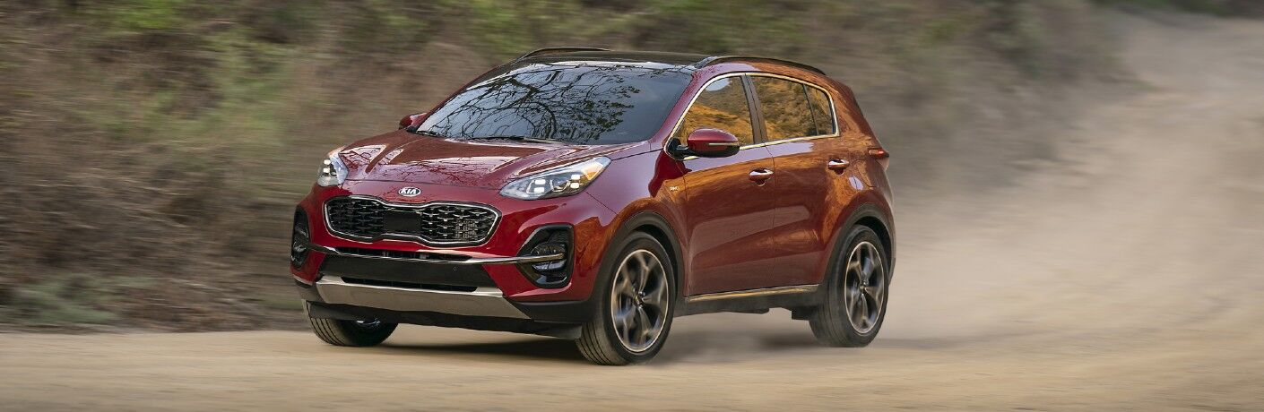 Red 2021 Kia Sportage driving on a dusty road