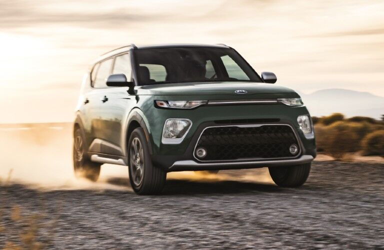 Green 2021 Kia Soul driving on a gravel road