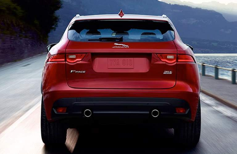 attractive rear end and tailgate of the 2018 Jaguar F-PACE as it drives by the water