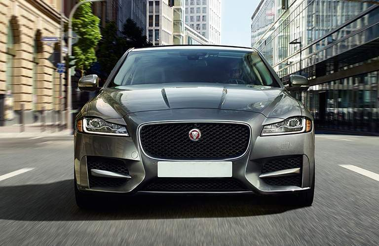 front grille of the 2018 Jaguar XF Sportbrake driving while it has city buildings on either side