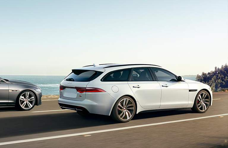 side view of a white 2018 Jaguar XF Sportbrake driving in front of the water