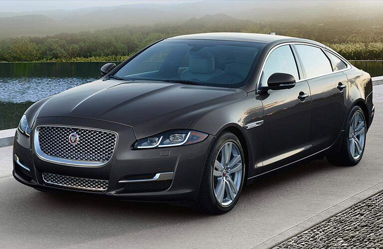 side and front view of the 2018 Jaguar XJL parked by water