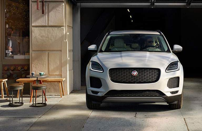 front view of the 2018 Jaguar E-PACE driving out a parking garage near a bistro