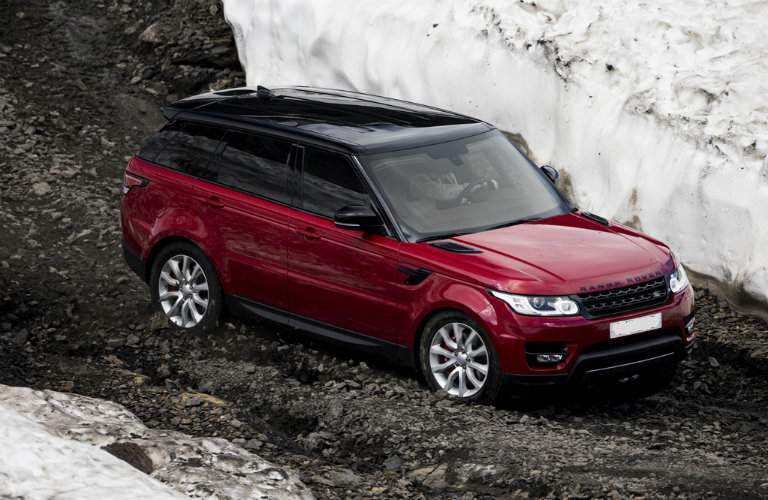 side view of a red 2017 Land Rover Range Rover Sport driving by snow