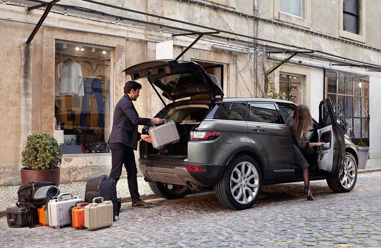 man loading luggage into the 2017 Land Rover Range Rover Evoque while a woman gets into the passenger seat