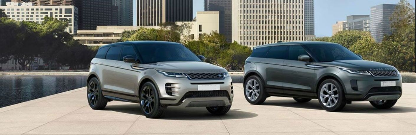 two range rover evoque models parked in front of kansas city skyline