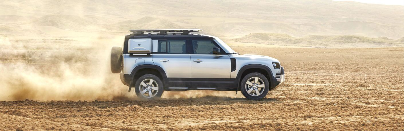 profile of 2020 land rover defender driving on sand
