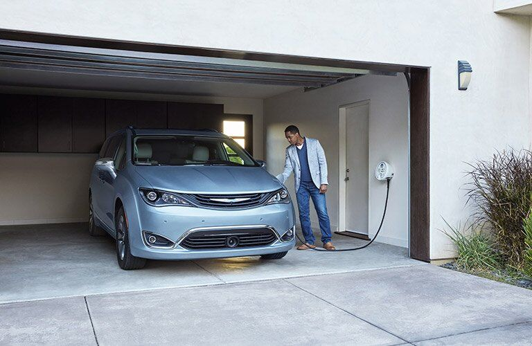 2017 Chrysler Pacifica Hybrid charging in a garage, an owner plugging it in