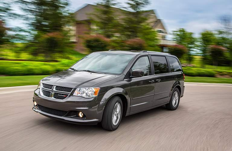 side view of a black or grey 2017 Dodge Grand Caravan on a rural road in front of a house
