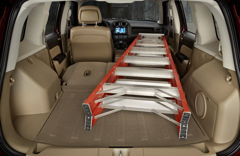 the 2017 Jeep Patriot with all the seats folded down holding a ladder