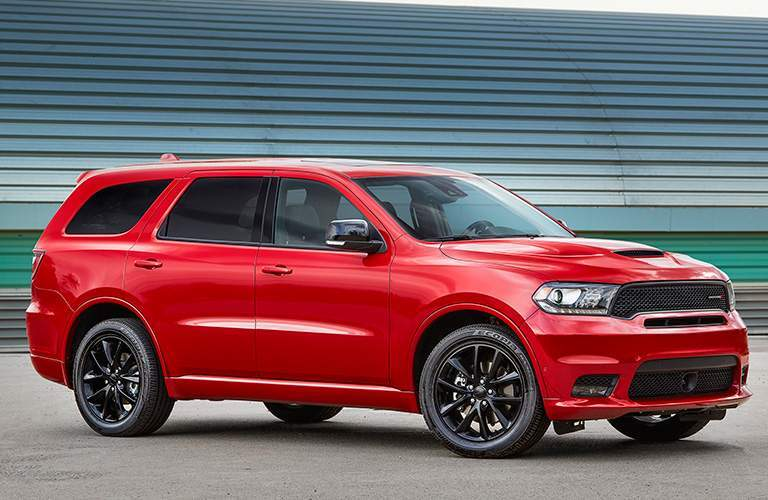 side view of a red 2018 Dodge Durango in front of a metal garage door