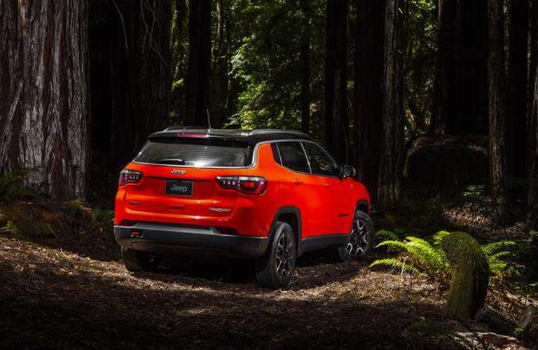 rear view of an orange 2018 Jeep Compass in the woods