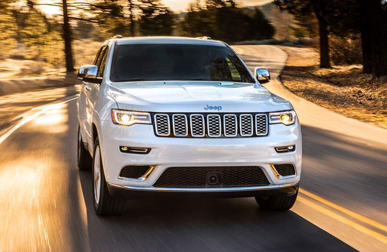front of a white 2018 Jeep Grand Cherokee driving through forest on a road