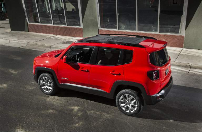 side view of a red 2018 Jeep Renegade driving in the city