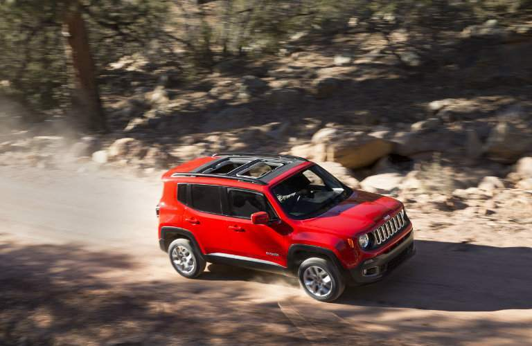 red 2018 Jeep Renegade with the sunroof open on a dirt road