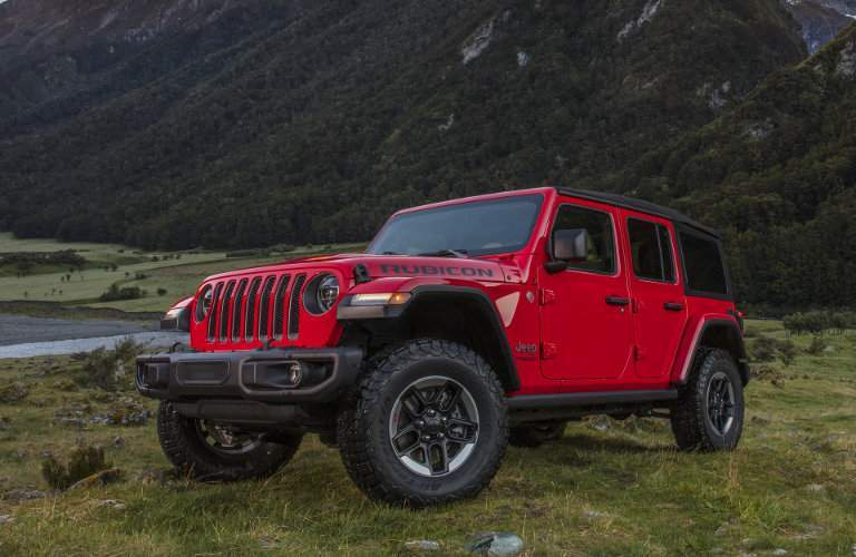 side view of a red, four-door 2018 Jeep Wrangler Rubicon