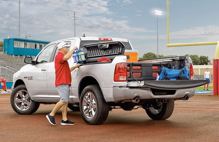 white 2018 Ram 1500 loaded with tailgating materials, man using the RamBox