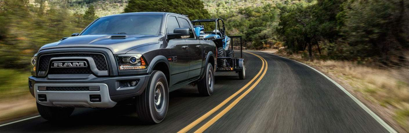 A view of the 2018 Ram 1500 on the road towing a four-wheeler. The 2018 Ram 1500 has already arrived in St. Paul MN