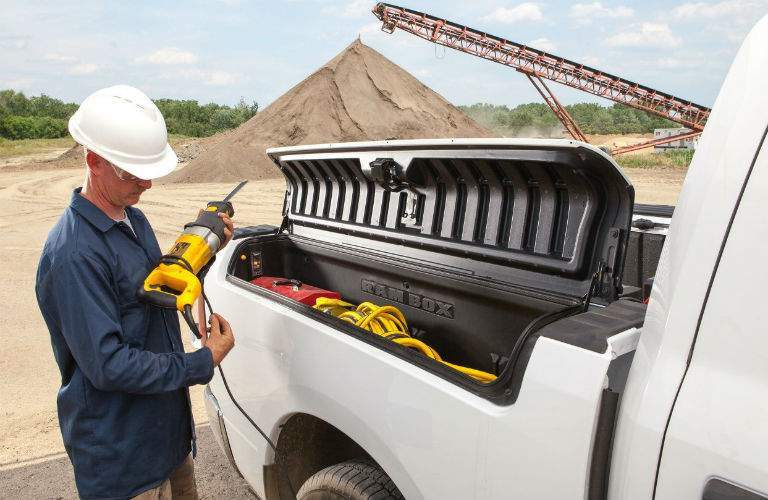 man on a work site getting power tools from the RamBox of a 2018 Ram 1500