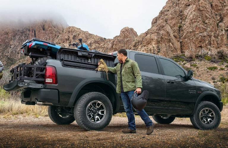2018 Ram 1500 equipped with the RamBox storage system and loaded with a fourwheeler with a man standing next to the truck