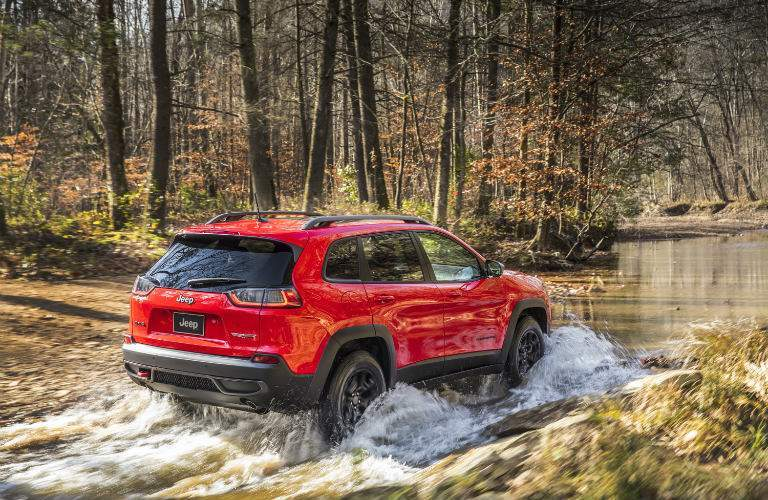 rear and side view of the 2019 Jeep Cherokee Trailhawk driving through a stream