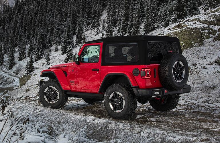 side view of a red 2019 Jeep Wrangler on a snowy mountain