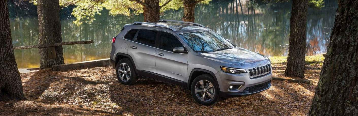 silver 2019 Jeep Cherokee parked in the forest by a lake