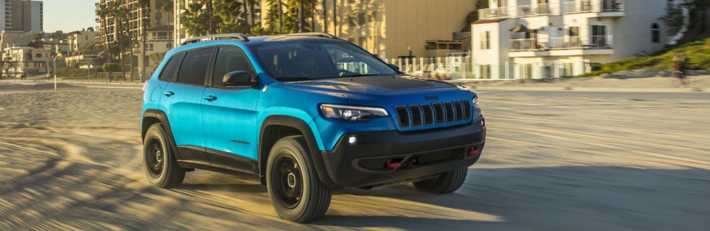 Blue 2020 Jeep Cherokee driving through sand