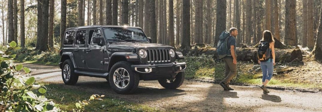 2020 Jeep Wrangler Unlimited in forest with hiking couple