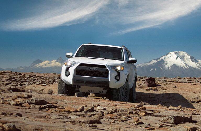 2016 Toyota 4Runner in while perched on some rocks near the mountains